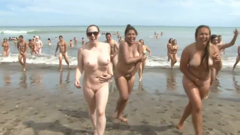 Huge group of nudists swim in the ocean