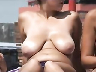 Chubby nerd smears her tits with sun cream