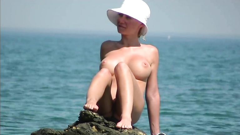 Naked lady at the ocean has amazing big tits