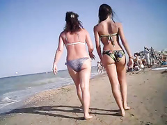 Bikini women take a stroll down the beach