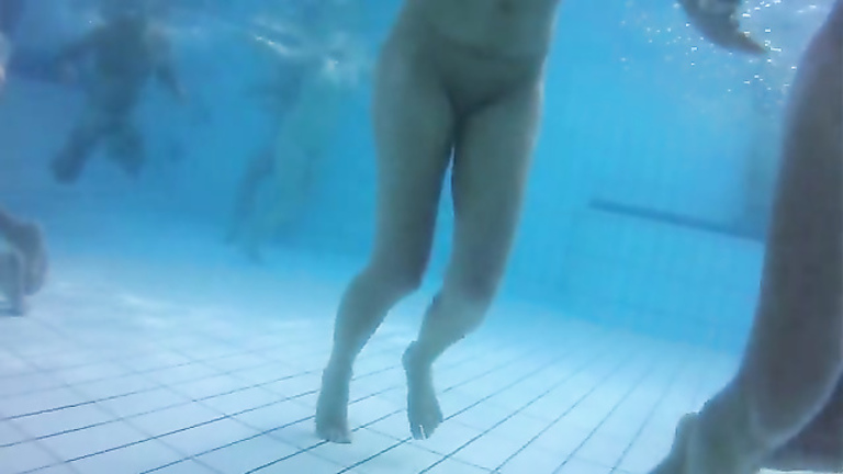 Underwater view with skinny dipping nudist women and men